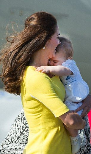 In mummy's arms: A sleepy George snuggles up to mother Kate as they leave the aircraft
