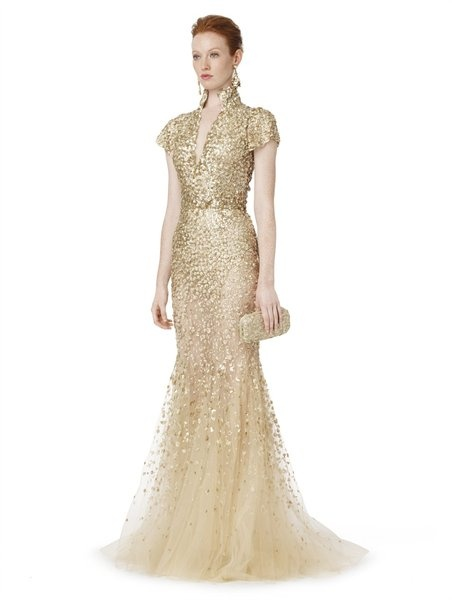 OSCAR DE LA RENTA  Gold Cap Sleeve V Neck Gown with Floral Embroidery  A sophisticated and flattering silhouette serves as the perfect backdrop for the thousands of tightly encrusted golden floret paillettes. A magical effect requiring at least 1,160 hours of hand embroidery to create.
