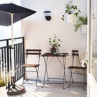 A balcony with a parasol and foldable table and chairs