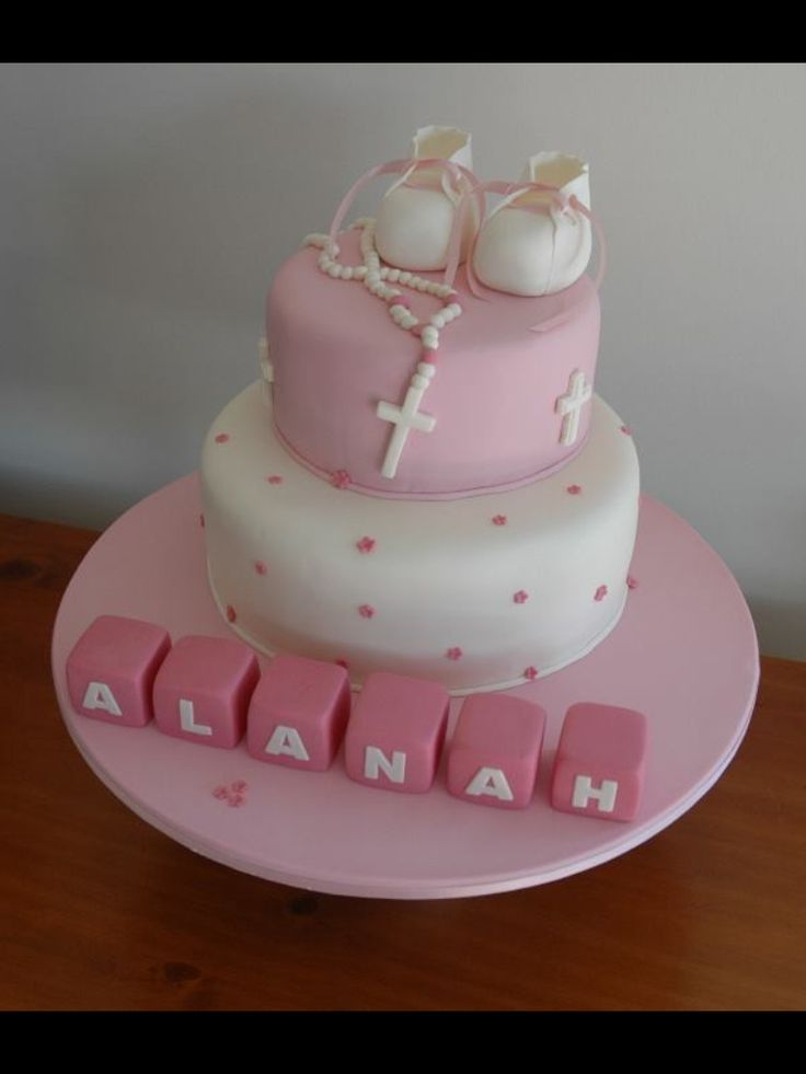 Pink baptism cake with rosary and booties