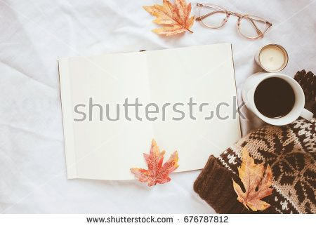 Autumn lifestyle concept, blank notebook and eyeglasses with knitted hat on white bed sheet background and maple leaves
