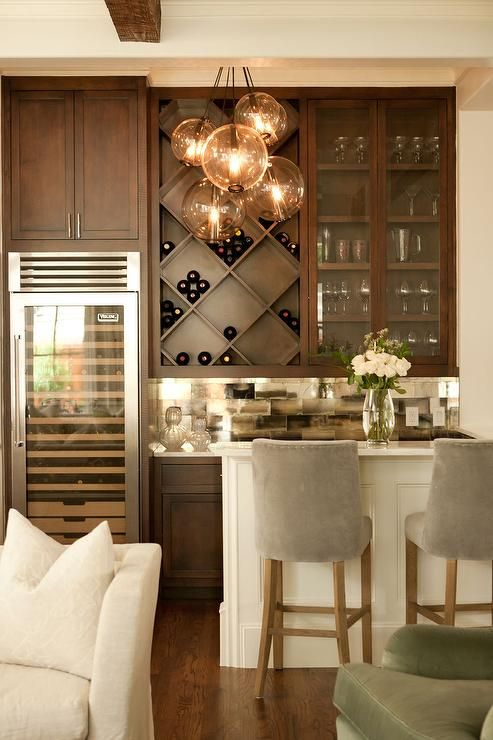 Chic living room bar features dark stained shaker cabinets paired with  white marble countertops .