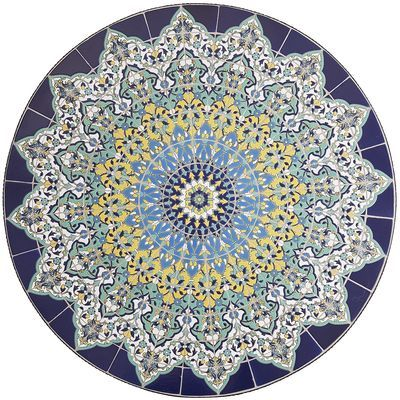 """In Spanish, the name Emilio means """"flattering""""—which is a great way to describe our dining table. Inspired by the stunning rose windows often found in cathedrals, its tabletop features a bright mosaic of hand-painted tiles and sits atop a scrolled iron base that was wrought by hand. Flattering is actually an understatement."""