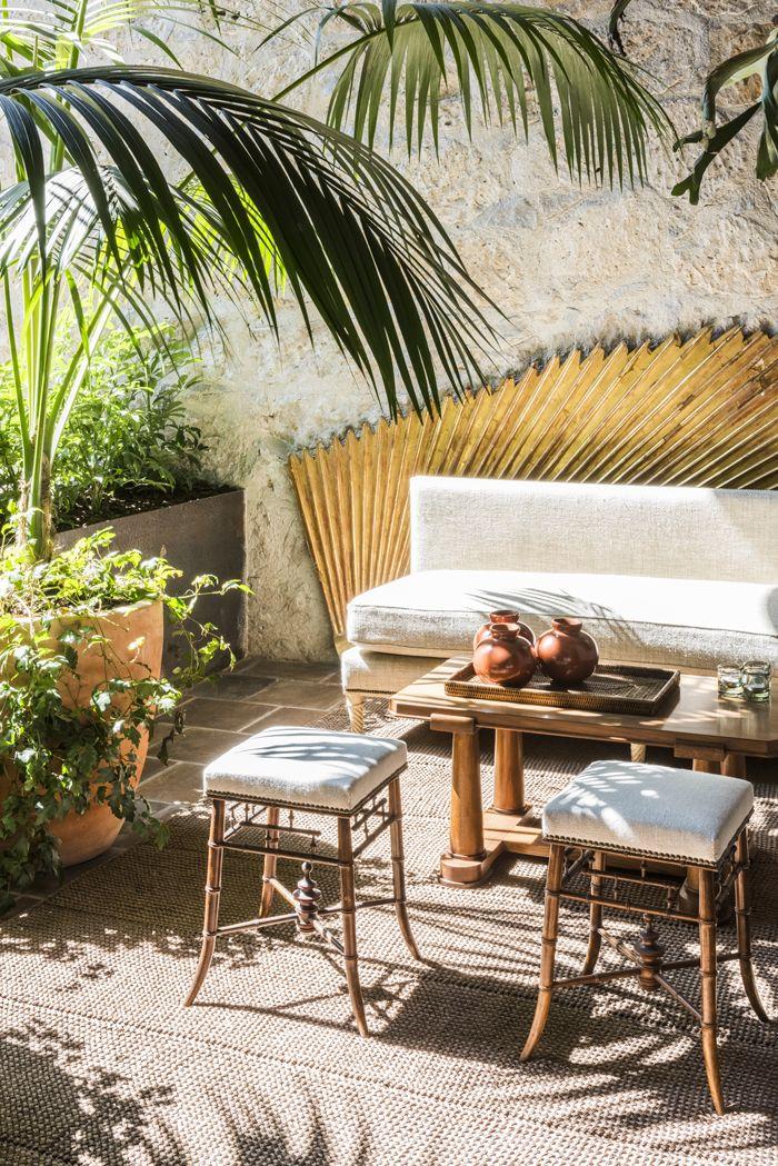 dans le salon du patio derriere une banquette et des tabourets en bambou habilles de tissu pierre frey un panneau decoratif en bois dore galerie
