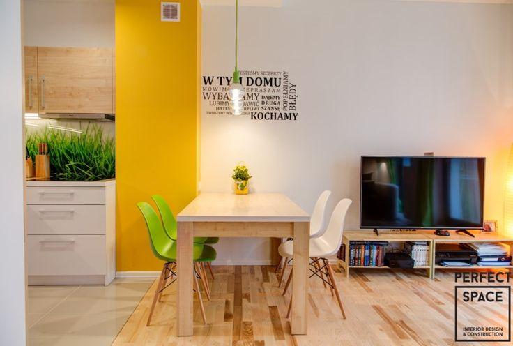 Kącik jadalniany, który stanowi granicę pomiędzy kuchnią a salonem. Punktowe oświetlenie nad stołem oraz motywujący napis na ścianie tworzą oddzielną strefę jadalnianą.