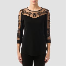 Joseph Ribkoff's casual fit top features sheer upper chest, shoulders and sleeves adorned with floral embroidery and black trim at the rounded neckline.