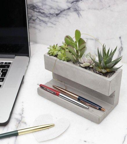 Ce rangement en béton est doté d'un emplacement pour des plantes grasses et/ou des cactus en plus d'une place pour vos bricoles de bureau.