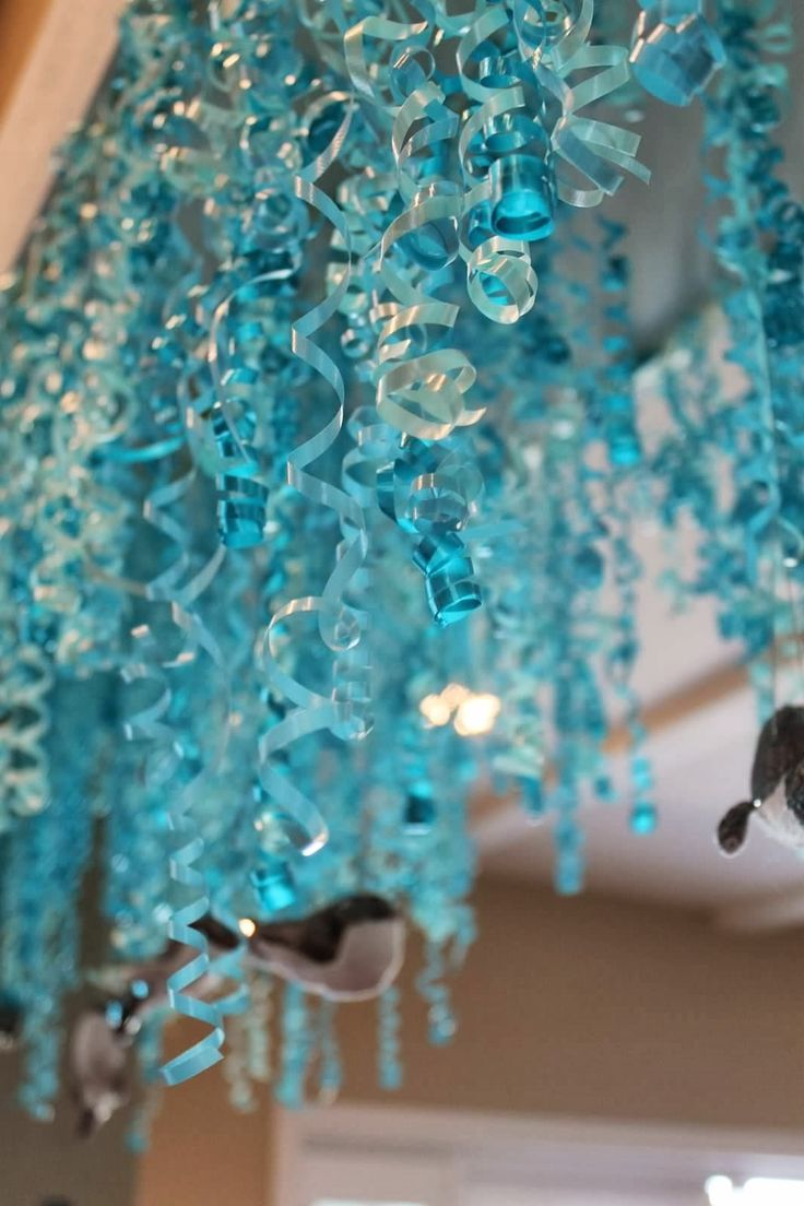 under the sea little mermaid first birthday party curling ribbon hanging from ceiling with sequin whale and fish ornaments