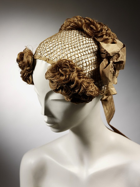 1840 Silk hairnet made of knotted silk mesh with false curls at the sides of the forehead and a clump of curls and brown silk ribbon behind