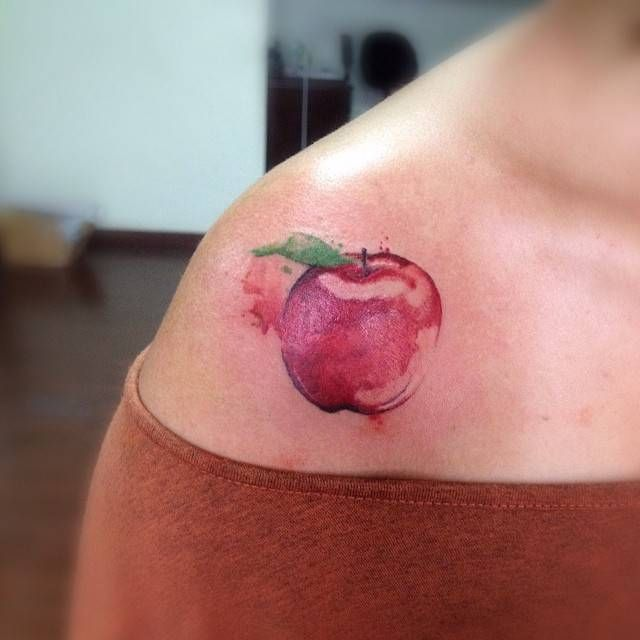 Watercolor style red apple tattoo on the right shoulder. Tattoo artist: Victor Octaviano