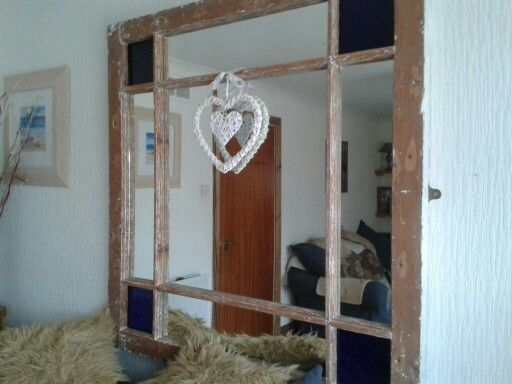 Large mirror made from reclaimed window with coloured glass in the corners.
