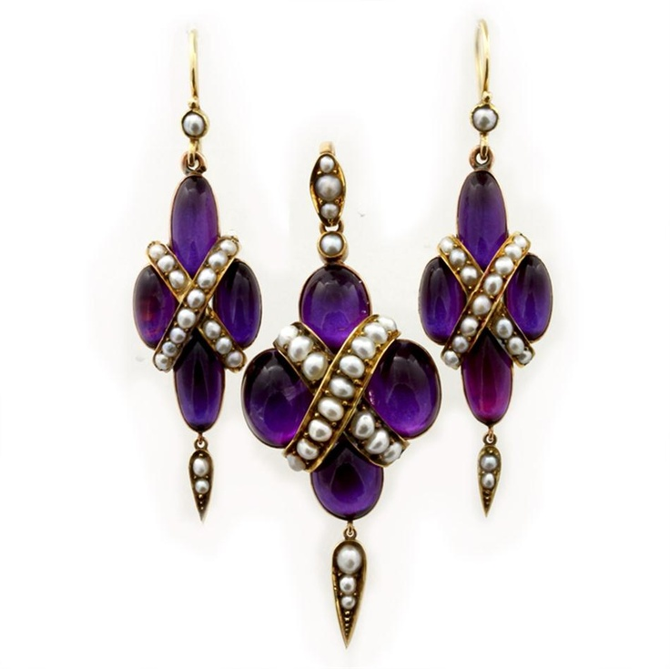 An early Victorian demi-parure comprising an amethyst and pearl pendant and earrings, each piece set with four cabochon cut amethysts in quatrefoil design between half pearl straps, mounted in gold, the pendant with a locket compartment to the reverse, suspended from a pendant loop set with three half-pearls, with a matching drop underneath, the earrings of a similar design, circa 1840, gross weight 23.2 grams.