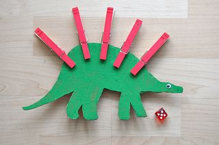 """Roll a dice then peg the correct number of pegs onto the dinosaur ("""",)"""