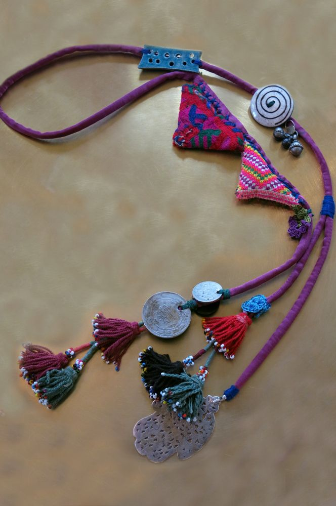 ETHNIC TREE: necklace made with hand-dyed Chinese silk. The sterling silver piece is an old Amazigh (Berber) hamsa. The coins are Ottoman and over 100 years old. the tassels are Uzbek and the embroidered triangles Thai from the Hill Tribes. The button is Nepali and made of Yak horns and the piece of pottery is designed by Lamia Beydou
