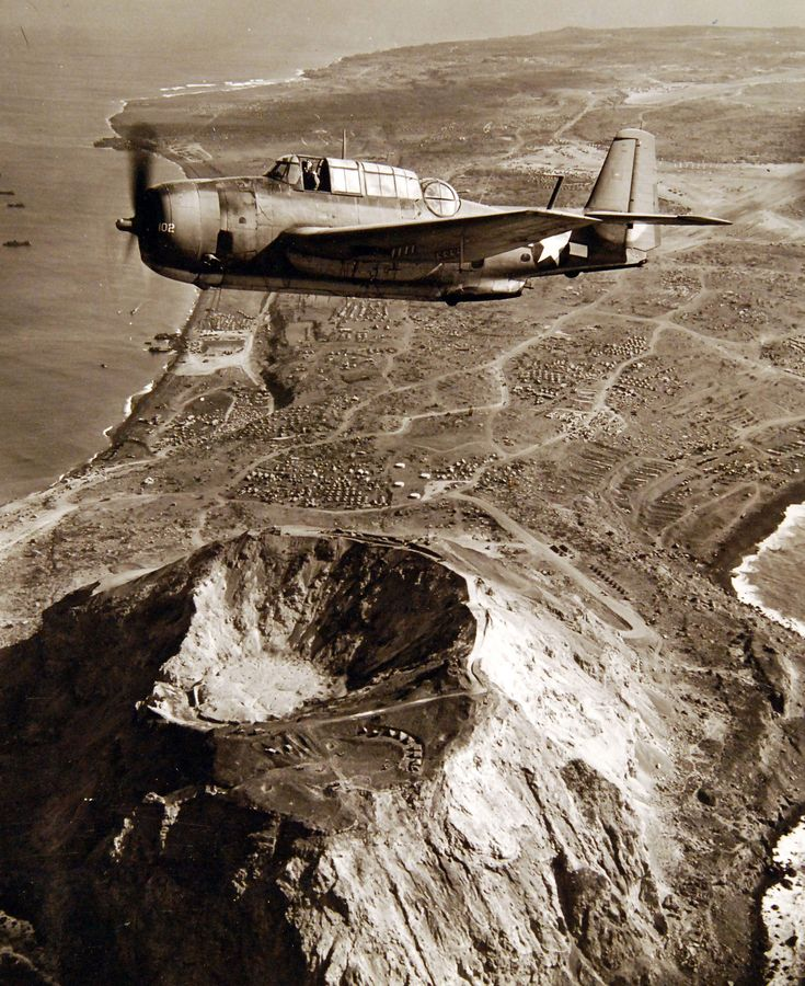 Battle of Iwo Jima, March 1945. TBM aircraft flying over Mt. Suribachi shortly after Iwo Jima was secured. Photographed by the Steichen Photograph Unit, March 1945. TR-13268. Official U.S. Navy Photograph, now in the collections of the National Archives. (2018/02/14).