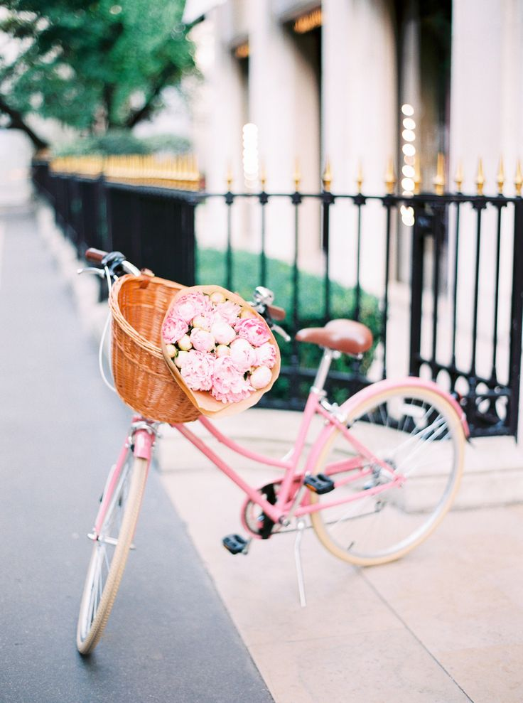 Pink bicycle with a basketful of flowers