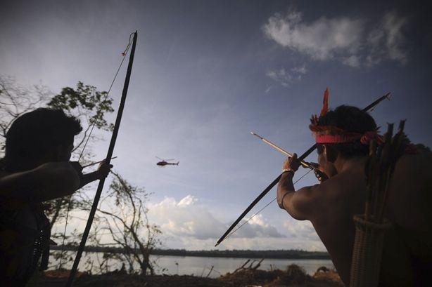 Carica, fuoco Con l'arco puntato contro un elicottero della polizia, due indigeni protestano contro la costruzione di un impianto idroelettrico e della diga di Belo Monte, sul fiume Xingù nell'Amazzonia brasiliana. Secondo gli attivisti il progetto devierà l'80% dell'acqua del fiume, sommergendo un tratto di foresta pluviale e prosciugando un'ansa del fiume che attualmente garantisce la sussistenza di centinaia di famiglie. REUTERS/STRINGER Brazil
