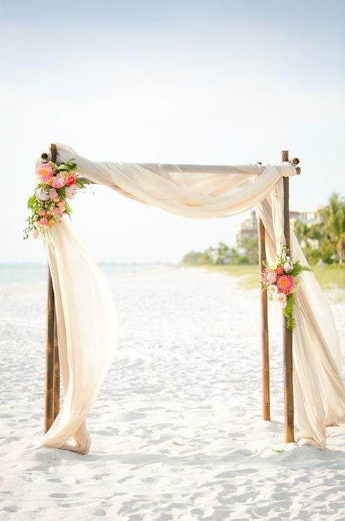 For a beachfront wedding, nothing looks more chic than sheer fabric draped over bamboo posts.