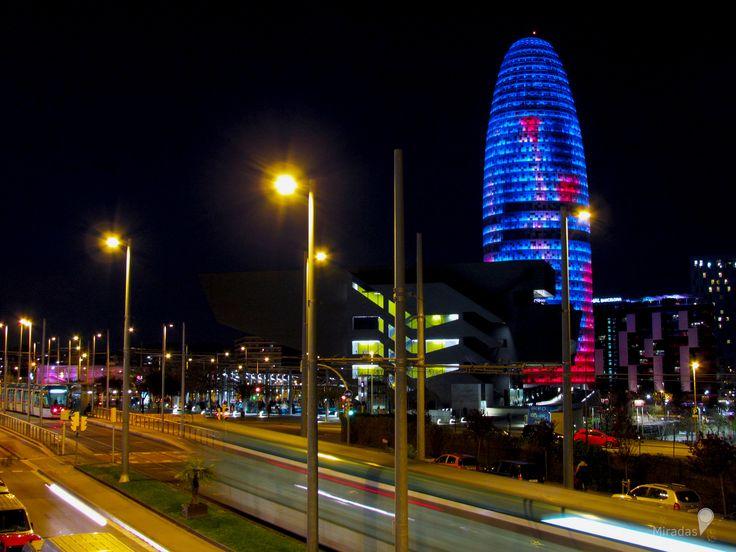 https://flic.kr/p/UL26h4 | La noche de colores | Uno de los elementos más característicos de la torre Agbar es su iluminación nocturna, la cual le da un toque de color a la noche en Barcelona.  La torre dispone de más de 4500 dispositivos luminosos de tecnología LED, que se pueden poner en funcionamiento de forma independiente y que posibilitan la generación de imágenes luminosas en la totalidad de su fachada, el sistema permite reproducir 16 millones de colores, gracias a un sofisticado…