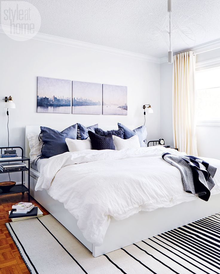 Nice bedroom design with white walls, amazing wall art and striped area rug
