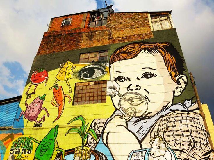 """16. Graffiti de Bebe y alimentos con el texto: """"Siembra Sano"""", en el muro de una casa de tres pisos en la Calle 26."""