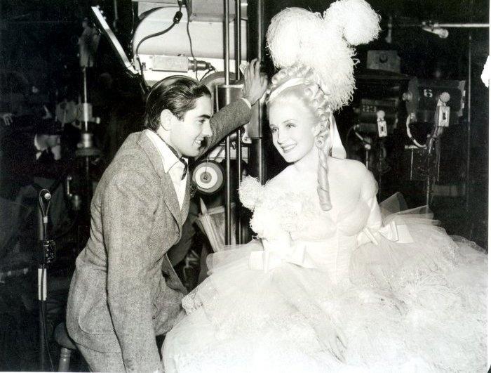 Norma Shearer en el set de rodaje de Maria Antonieta, con su compañero de reparto, Tyrone Power, el conde Axel Fersen.MGM, 1938. Vestuario femino de ADRIAN y masculino a cargo de Gile Steele.