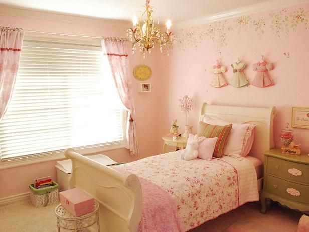 Feminine Fairytale:     This pink fantasy bedroom gets the shabby chic treatment from the well-chosen details. The elegant gold chandelier contrasts with the cottage-style sleigh bed, and the vintage doll clothes hanging above the bed perfectly complement the shabby chic bed linens.