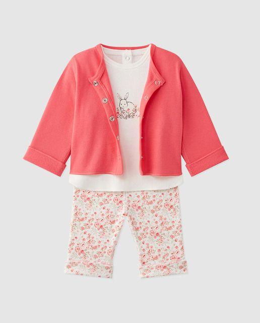 Conjunto compuesto por tres piezas en tono rosa. Una camiseta en color blanco, de manga larga y cuello redondo. Una chaqueta en color rosa, de manga larga y cierre en el delantero mediante automáticos. Un pantalón largo con estampado floral y elástico en la cintura.