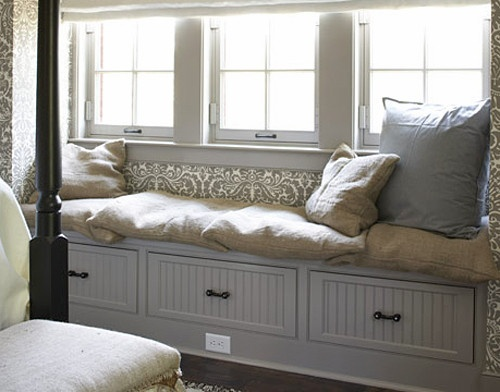 A window seat provides instant comfort and warmth in the bedroom; pillows covered in burlap add another layer of texture to the smooth, beadboard drawer fronts.