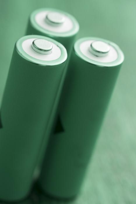 Three green rechargeable batteries stand with positive side up, isolated on a blurred green background - green energy concept - free stock photo from www.freeimages.co.uk
