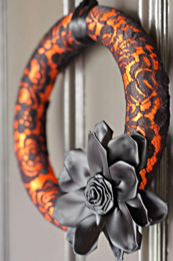 Halloween krans. Styropor krans omwikkeld met oranje satijnen lint. Daaromheen zwarte kant (va een oude jas) vastgezet. De bloem is gemaakt van zwart satijn
