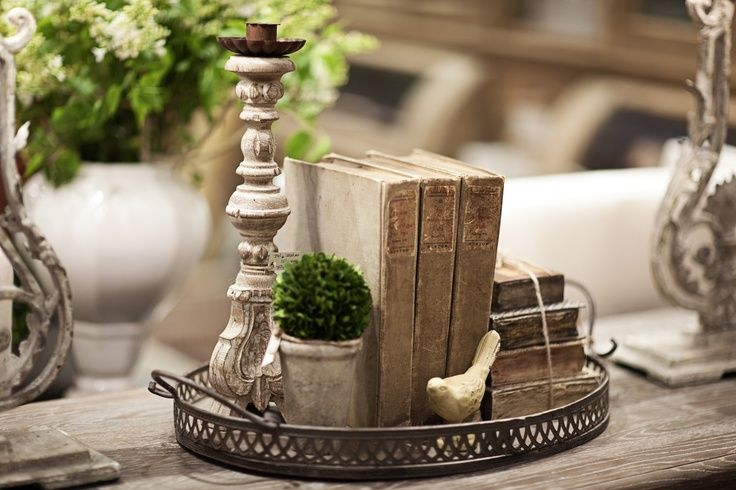 decorating with silver trays | Here a group of books ties together, candlesticks and a little pot and ...