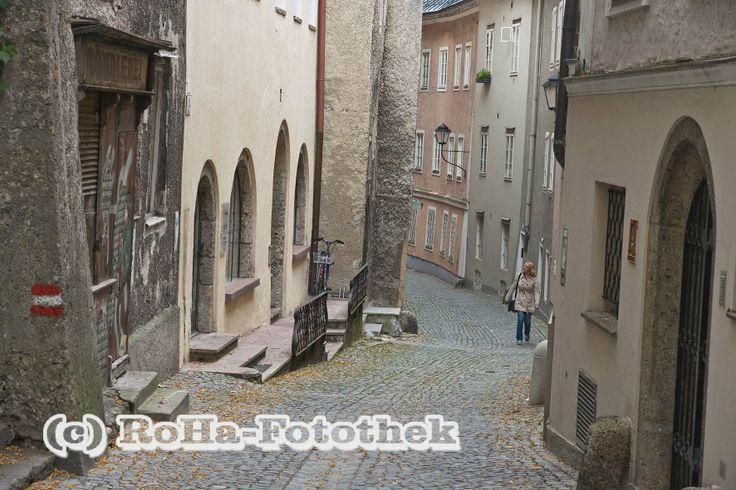 Salzburg - die Steingasse - Ganz eng schmiegen sich die Häuser auf der einen Seite an den Fels des Kapuzinerberges und auf der gegenüberliegenden Straßenseite hatten die meisten Häuser in den Jahren vor der Regulierung 1862 einen direkten Zugang zur Salzach.  http://www.roha-fotothek.de/index.php?id=164