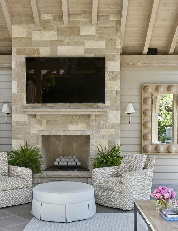Wonderfully appointed covered patio with a sloped ceiling features a cream stone fireplace fitted with a large flat panel television and positioned between oil rubbed bronze sconces mounted to a taupe shiplap trim.