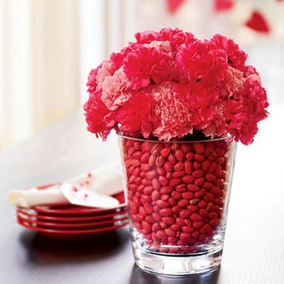 One large clear vase and one small vase inside filled with water then fill the space in between with red pistachios. Add flowers to small vase!