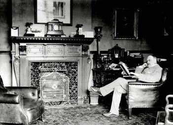 W. H. Allen reading in the library at Bromham House [Z50/21/30]
