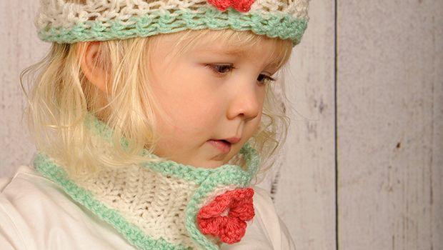 Een gehaakte witte sjaal met roze bloem voor je kleine meid! Het is een col sjaal en geschikt voor peuters. Bekijk het patroon hier!