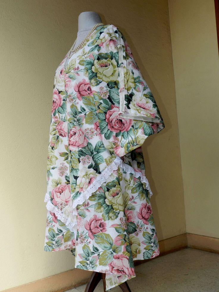 Robe grande taille fleurie de roses. Réalisée en imprimé coton/synthétique  doublé de coton. Cette robe est ouverte sur les épaules et les bras, le maintien se fait par des ganses. Les manches ont une découpe en ailes de chauve souris. Insertion d' un ruban de broderie anglaise.   Hauteur de robe 108 cm . Tour de bassin 128 cm ce qui correspond à du 52 . Prix: 69 euro