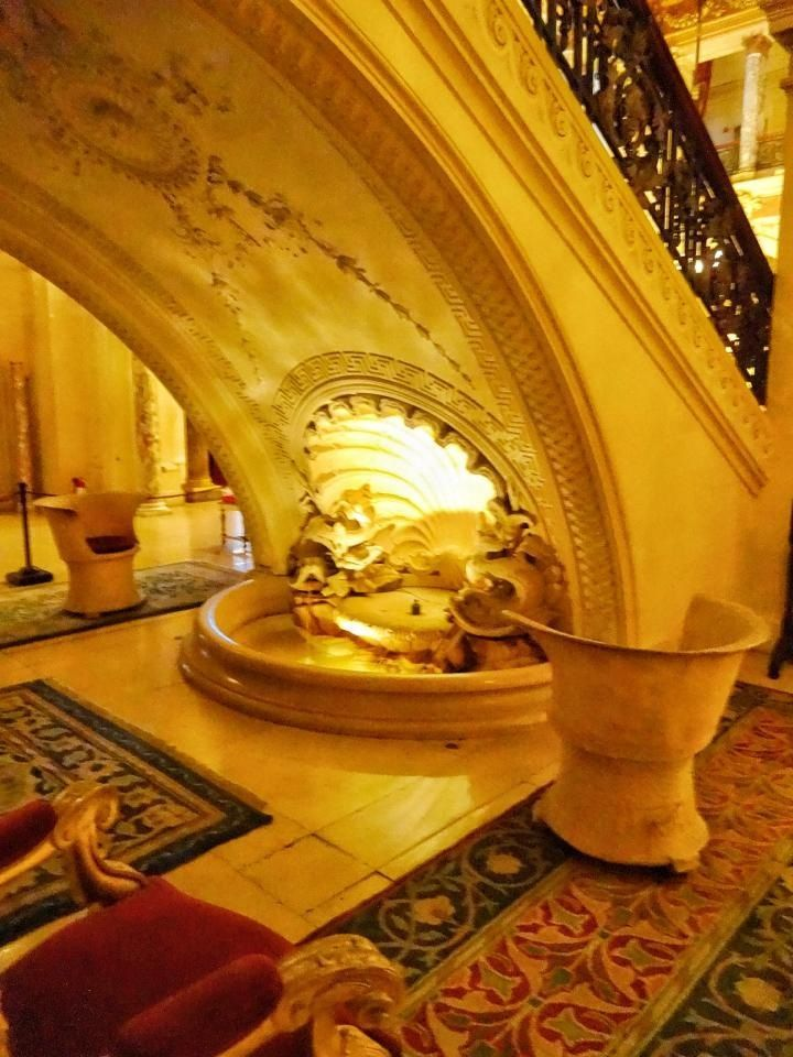 Fountain and sitting area underneath grand staircase in entrance hall.