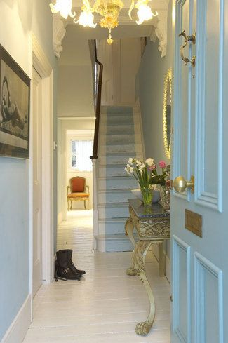 Love this blue with the gold console, white wood floors and painted runner on the stairs
