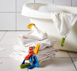 Pile de petites serviettes à côté d'une baignoire pour bébé