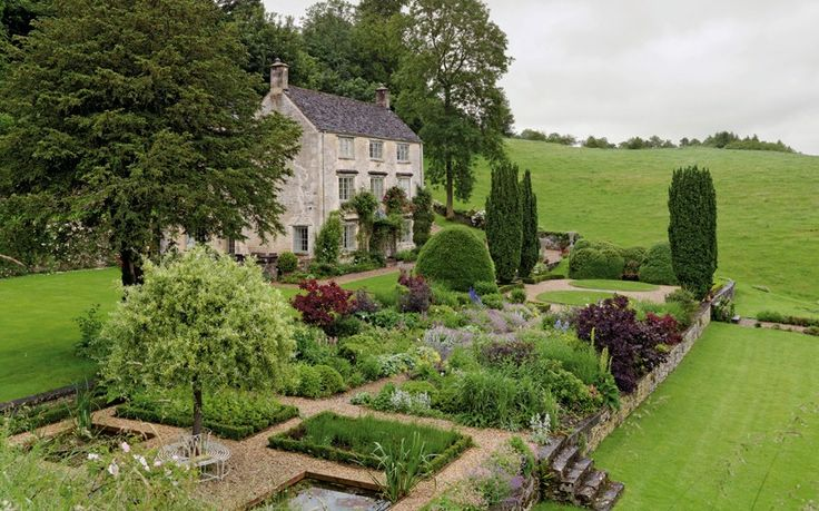 The 200-year-old house, built from Cotswold limestone, sits in a valley in Gloucestershire on a site that has been occupied since the 15th century. The garden has been re-planted by the current owners - developing a rose garden, orchard and vegetable garden. The formal garden in front of the house looks out over a wooded valley, part of its seven-acre estate; the small summerhouse behind it was originally built for a footman.