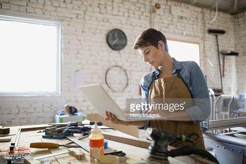 Stock Photo : Female carpenter using laptop in workshop
