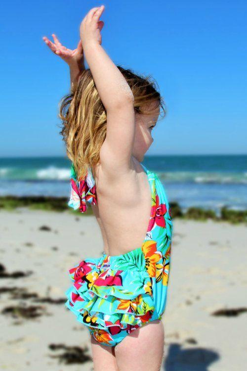 $49.95  - Aqua swimsuit with fluoro pink, yellow and orange hibiscus flowers  - 3 ruffles on back  - Adjustable halter neck  - Generous fit, with 2 seasons' growth  - Nylon lycra with UPF 50+  - Sizes 1, 2, 4, 6 www.heavenleeswim.com