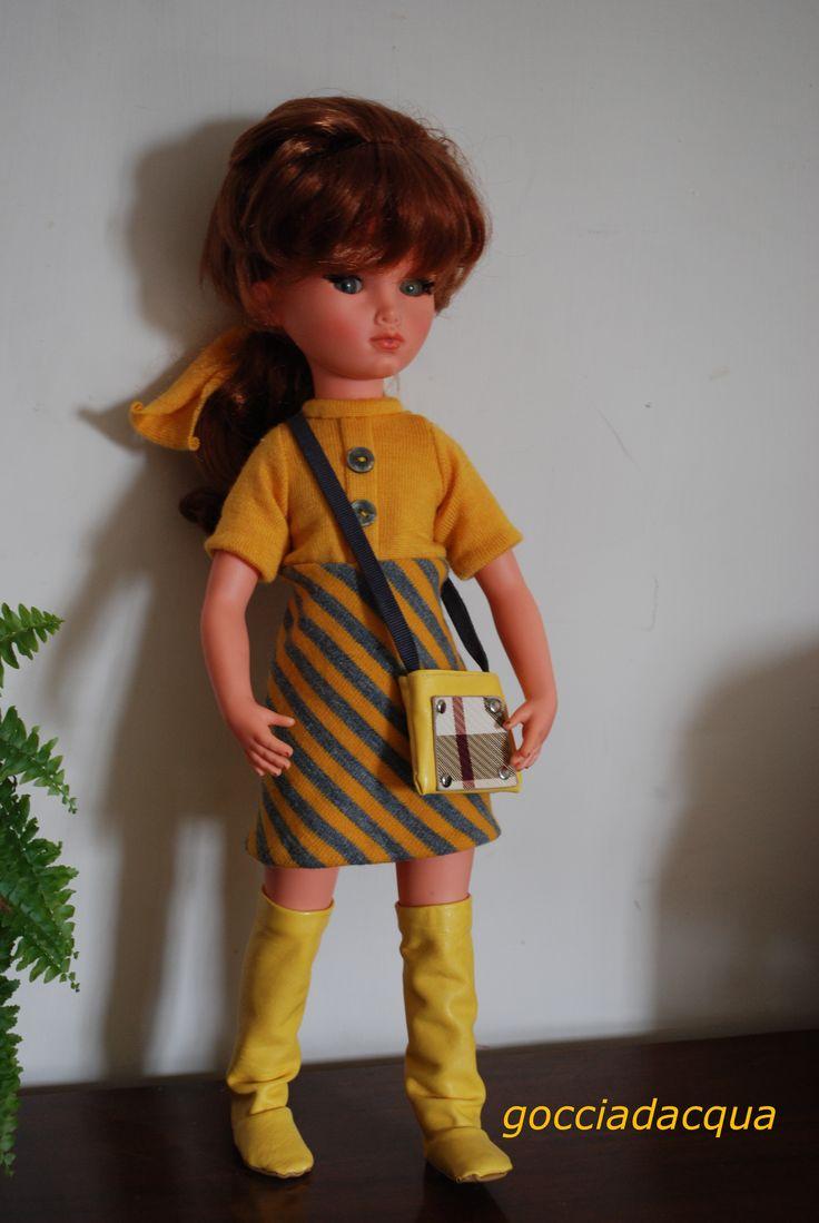 Sylvie OOAK con capelli rosso tiziano e frangetta indossa una riproduzione di 'Caponero' 1968 abbinata ad alti stivali gialli.