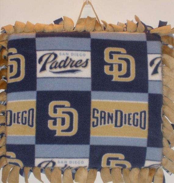 """Fleece Tied San Diego Padres Stadium Seat Cushion. Back is a tan fleece.   2"""" High-Density foam. Carrying Strap Included. Finished product measures 19"""" x 17"""".     Great for those 'hard', 'cold' bleachers and stadium seats! Show your 'Team Spirit'!    Spot cleaning recommended, but if machine wash needed: untie top of cushion and remove foam. Machine Wash - Cold. Tumble Dry - Low. Replace foam and re-tie.     Blankets, Scarves, and Pillows also available!!! Other Teams also available!!!"""