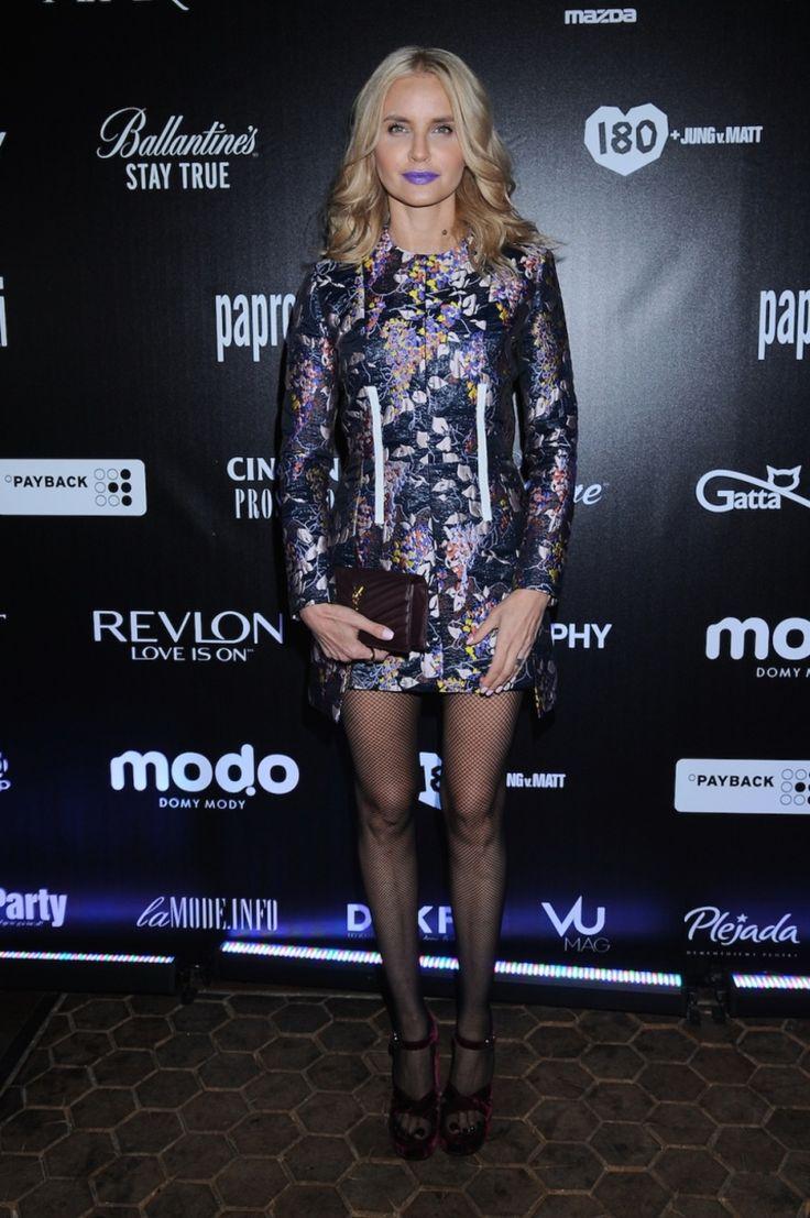 Joanna Horodyńska w metalicznej sukience, mała bordową torebką, fioletowe usta