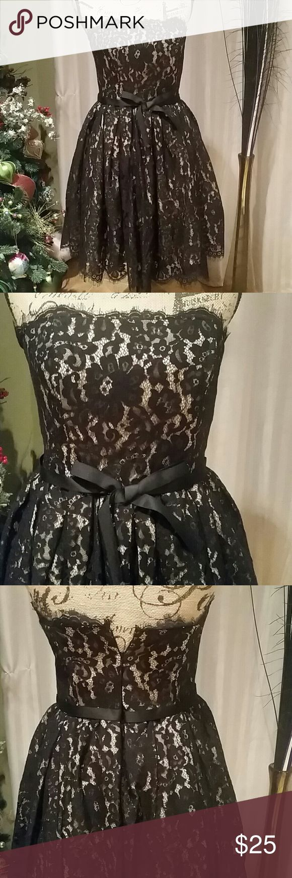 Black lace holiday dress Dress is black lace with nude lining.   Skirt is lined and has tulle for fulness.   Ribbon around waist.  Boning on top part of dress in breast area and on sides.   Zips up the back. Genuine Denim Co. Dresses Strapless