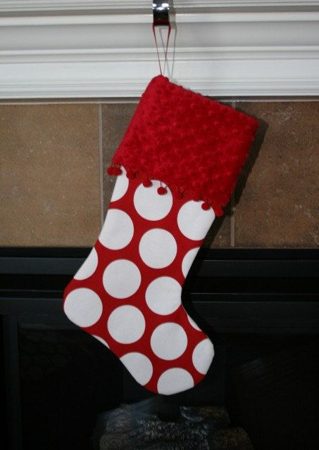 Red modern christmas stocking with white dots and ball fringe