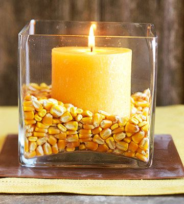Corn & Candles  Fall-colored candles pay homage to the harvest when surrounded by dried corn in a plain glass jar. What could be simpler?